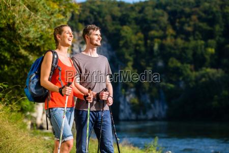 man and woman hiking at river