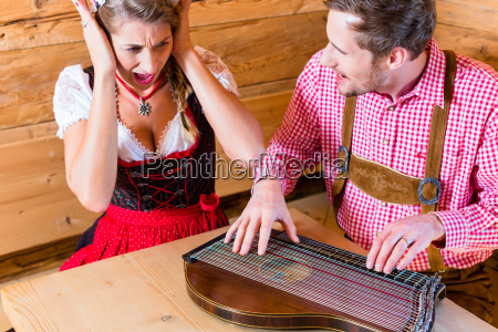 man playing poorly on zither in