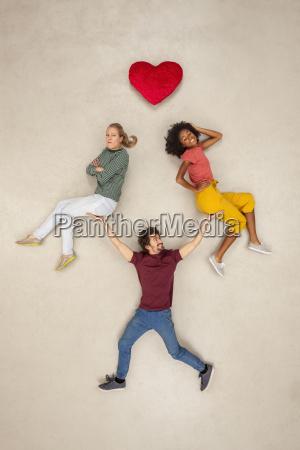 man balancing two women on his