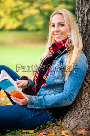 woman reading book in autumn park