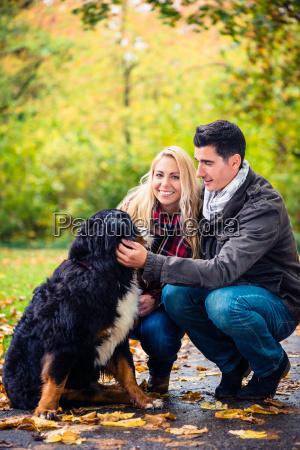 couple with dog enjoying autumn in