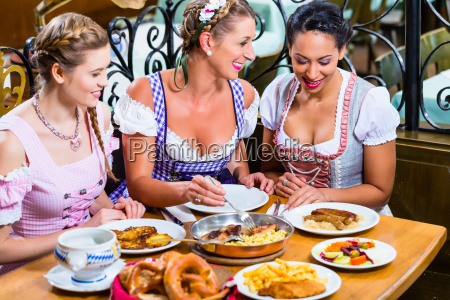 women in bavarian pub eating food