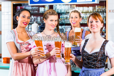 innkeeper and guests drinking beer in