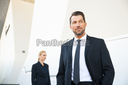confident businessman and businesswoman outside office