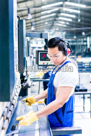 two industrial workers inspecting work piece