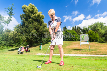 senior woman doing tee stroke on