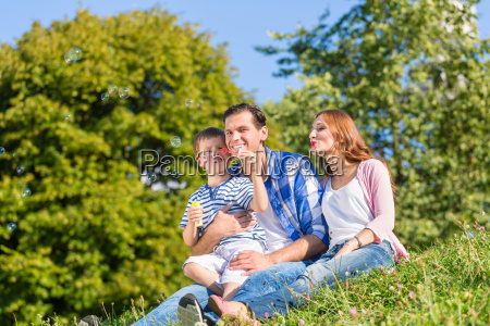 family sitting on meadow playing with