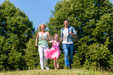 mum dad and daughter running on