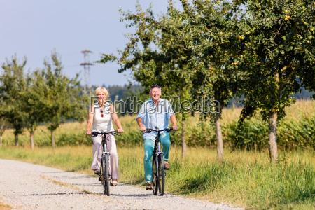 senior woman and man at bicycle