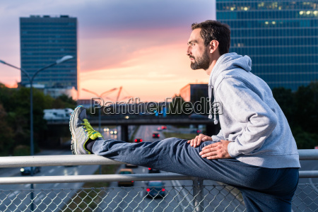 runner stretching in front of office