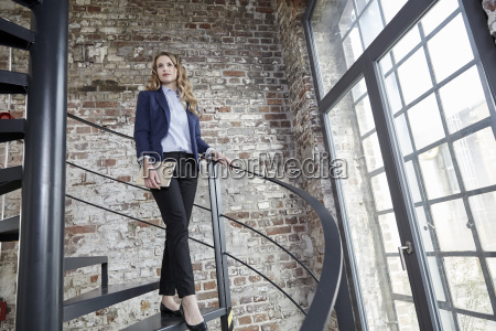 businesswoman walking down spiral staircase