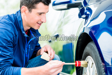 man cleaning the alloy hubs on