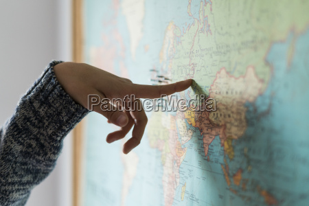 womans hand pointing on world map