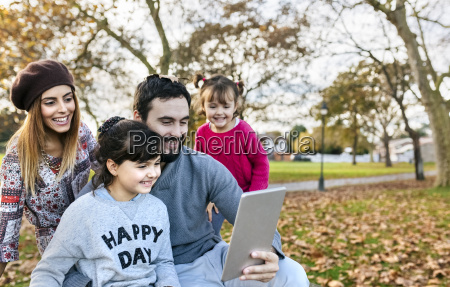 family with tablet in autumnal park