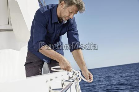 man on motor yacht tying a