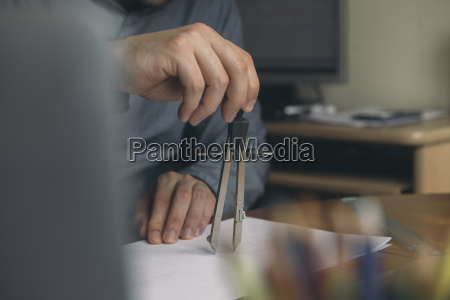 close up of man using compasses