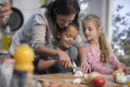 mother helping daughters in kitchen