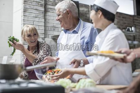 happy senior couple and female chef