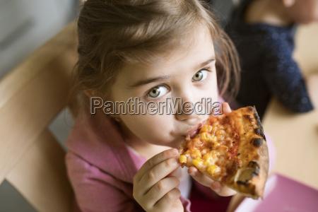 little girl at home eating slice