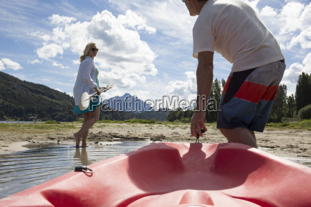 mature couple haul kayak out of