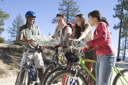 multiethnic friends with bikes and map