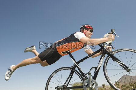 male cyclist balancing his stomach on