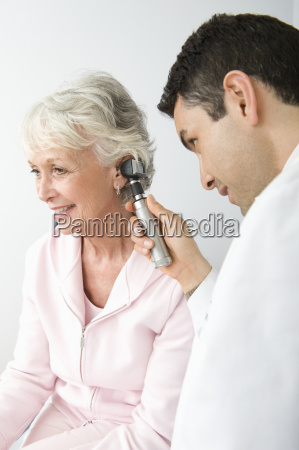 doctor checking patients ear using otoscope