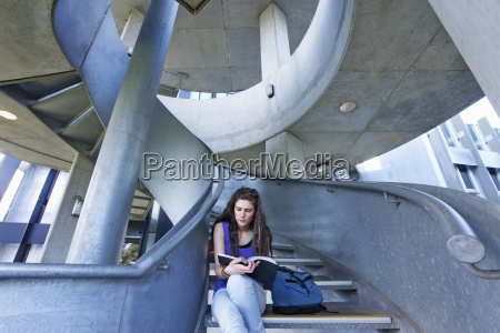 female student reading on staircase