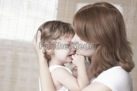mother comforts crying baby girl