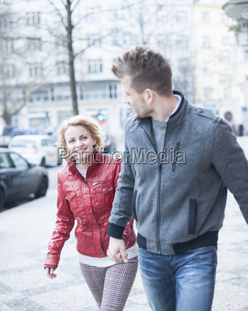 happy young couple holding hands while
