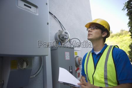 maintenance worker reading meter of solar