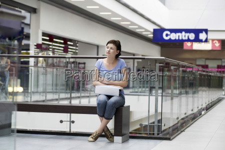 woman with paper bag sitting in