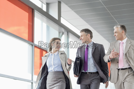 businesspeople communicating while walking on railroad
