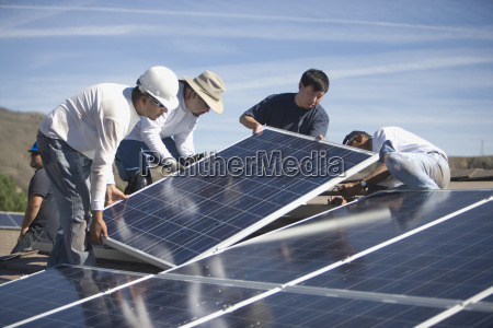 engineers placing solar panels on rooftop