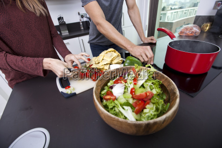 midsection of couple cooking together at