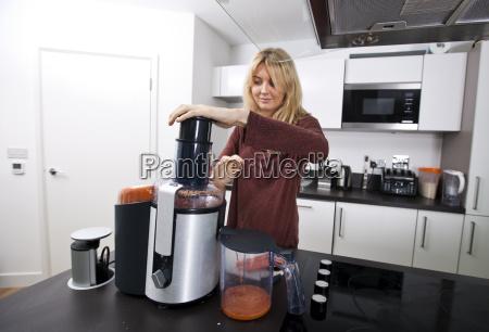 young woman juicing carrots at kitchen