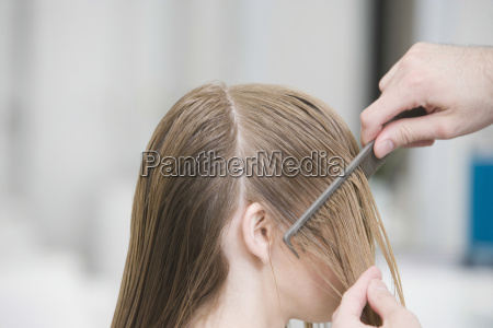 hairstylists hand combing clients hair before