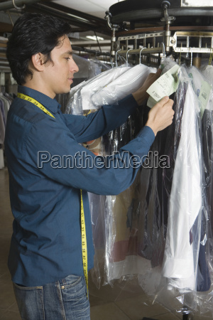 owner organising clothes on rail in