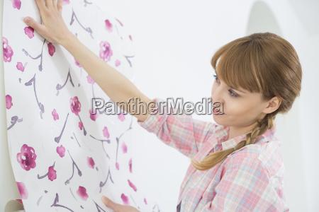 woman applying wallpaper on wall in