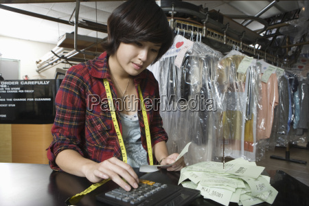 owner using calculator while holding bill