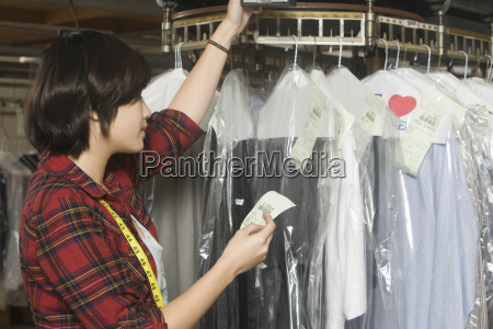 laundry owner reading receipt by clothes