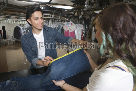 owner showing jeans measurement to client