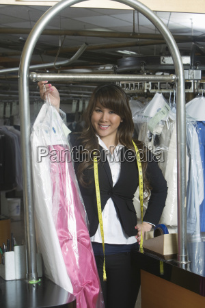 confident owner holding clean dress in