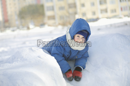 boy in jacket leaning on snow