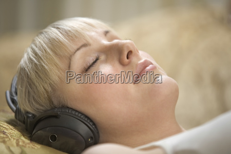 woman with eyes closed listening music