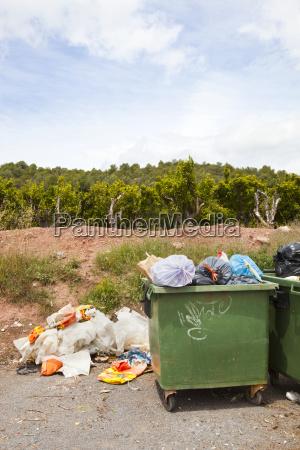 overflowing bins next to orange orchard