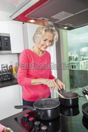 smiling senior woman preparing food at