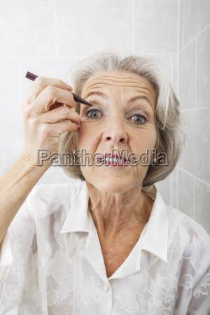 portrait of senior woman applying eyeliner