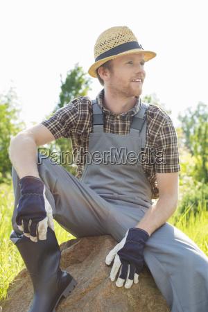 thoughtful gardener looking away while sitting