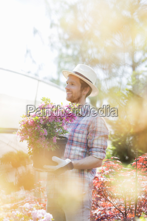 smiling gardener looking away while holding